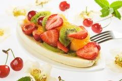 Banana split with fresh fruit. Banana split with strawberry, kiwi and orange slices Stock Image