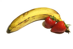 Banana and strawberries. Banana and two strawberries, shallow DOF royalty free stock photo