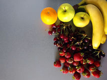Banana, strawberry, cherry, orange And apple on a gray background Royalty Free Stock Photo