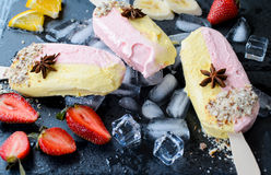 Banana and strawberry popsicles. On a blue background, selective focus Stock Images