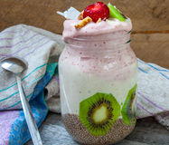 Banana-strawberry smoothie with kiwi, chia, nuts and coconut in a jar. Stock Photos
