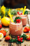 Banana and strawberry smoothie. Two Cold Strawberry Banana Smoothies in Glasses with Ingredients on Kitchen Table. Strawberry Bana Stock Image