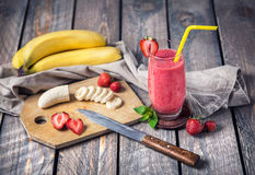 Banana and strawberry smoothie. On wooden background Royalty Free Stock Photography