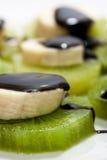 Banana tagliata impilata sul kiwi con la salsa di cioccolato Fotografia Stock