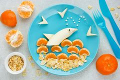 Banana tangerine corn flakes dolphin fish. Summer food art idea stock photos