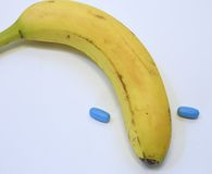 Banana with two blue pills for male problems Stock Photography