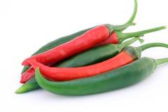 A banana vermelha e verde dos pimentões salpica com hastes verdes Fotos de Stock