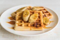 Banana waffle with caramel. On white plate royalty free stock photo