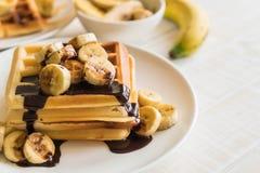 Banana waffle with chocolate. On white plate Stock Photos