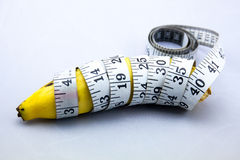 Banana wrapped up around with Measure Tape.  Stock Photos