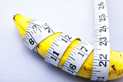 Banana wrapped up with Measure Tape.  Stock Image