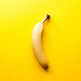Banana on yellow table. One banana on yellow table. Top view, with copy space Royalty Free Stock Images