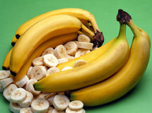 Bananas. Whole and sliced bananas on green background Stock Photography