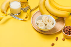 Bananas and almonds with measuring tape on yellow background wit Stock Image