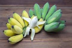 Bananas amarelas e verdes no fundo de madeira, fruto fotos de stock