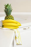 Bananas and ananas on kitchen's table Royalty Free Stock Images