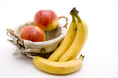 Bananas and apple. Refine ripe bananas and apple in the basket Stock Photos