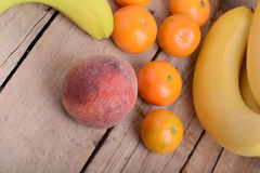 Bananas apple mandarin peach strawberry on wooden background as health food concept Stock Image