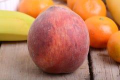 Bananas apple mandarin peach strawberry on wooden background as health food Royalty Free Stock Photos