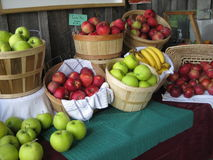 Bananas and apples. Baskets of bananas and a variety of apples at a local food stand Royalty Free Stock Photography