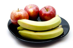 Bananas and apples. On black plate Stock Photo