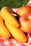 Bananas and apples in nature Royalty Free Stock Photo