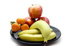Bananas and apples and orange. On black plate Stock Images