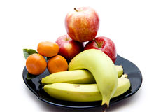 Bananas and apples and oranges. On black plate Stock Image