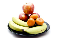 Bananas and apples and oranges. On black plate Royalty Free Stock Photo