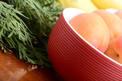 Bananas and apricots on red plate, close up Stock Photos