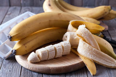 Bananas and banana slices on a wooden board. (6 Royalty Free Stock Photo