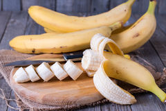 Bananas and banana slices on a wooden board Royalty Free Stock Image