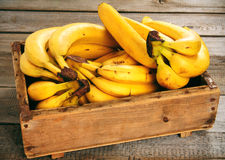 Bananas in a box. On a wooden background Royalty Free Stock Photo