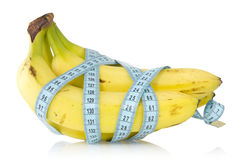 Bananas bunch wrapped with measuring tape Stock Photo
