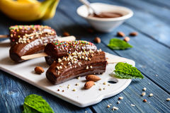 Bananas coated in chocolate and sprinkled with chopped almonds and colorful sprinkles Royalty Free Stock Image