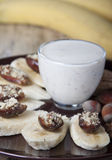 Bananas with dates   and a cup of yogurt. Royalty Free Stock Photography