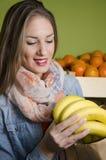 Bananas de compra da morena natural bonita Imagens de Stock