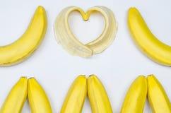 Bananas e coração da banana no branco Fotografia de Stock Royalty Free