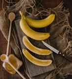 Bananas e fatias da banana em uma placa de madeira Fotos de Stock Royalty Free