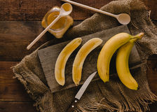 Bananas e fatias da banana em uma placa de madeira Imagens de Stock Royalty Free