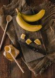 Bananas e fatias da banana em uma placa de madeira Fotos de Stock