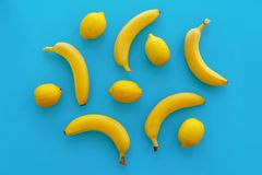 Bananas e limões amarelos no papel azul brilhante, configuração na moda do plano imagem de stock