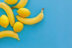 Bananas e limões amarelos no papel azul brilhante, configuração na moda do plano imagens de stock royalty free