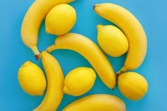 Bananas e limões amarelos no papel azul brilhante, configuração na moda do plano imagem de stock royalty free