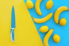 Bananas e limões amarelos no papel azul brilhante e na faca grande, tr fotografia de stock royalty free