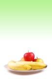 Bananas e maçãs frescas em uma placa da porcelana Imagem de Stock Royalty Free