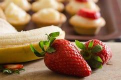 Bananas e morangos na parte dianteira banana, morangos e fotografia de stock royalty free