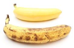 Bananas frescas e passados no fundo branco Fotografia de Stock Royalty Free