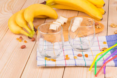 Bananas and glasses on the wood floor. Royalty Free Stock Photo