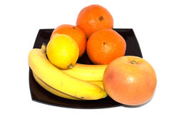 Bananas, grapefruit, lemon and orange on a black plate Stock Photos